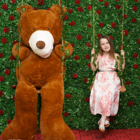 child on swing with large teddy bear