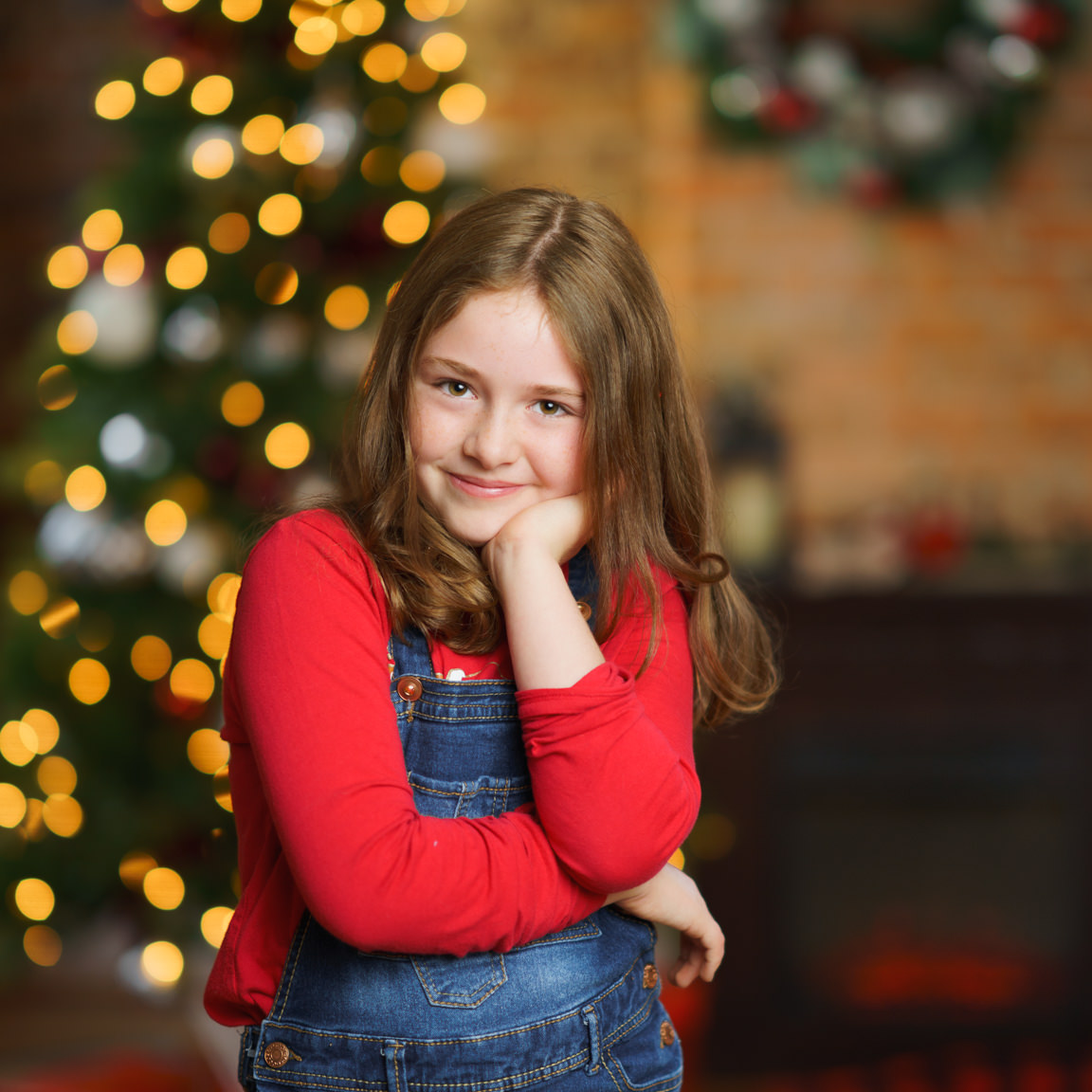 girl posing in front of Christmas tree