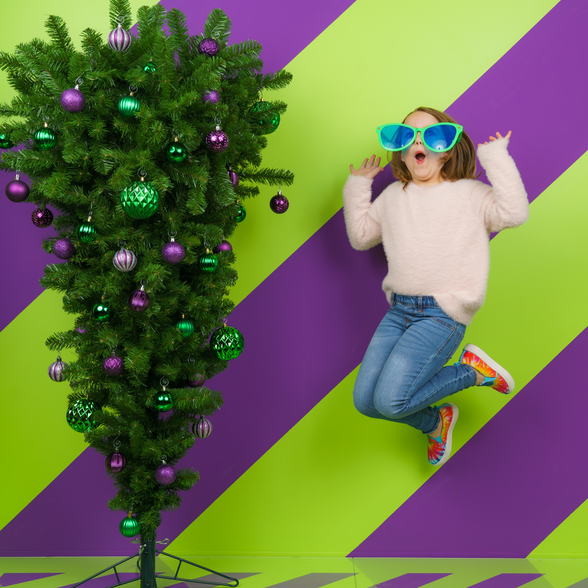 child jumping next to upside down Christmas tree