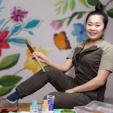 Rozzie Lee artist in front of her mural at snap foto club